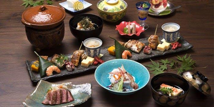 先付や焼物などの料理がそれぞれ器に盛られ、テーブルの上にずらりと並べられている。
