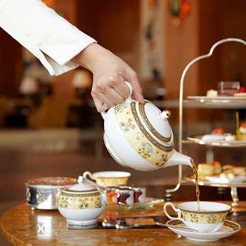 女の人がティーポットで紅茶を注いでいる写真