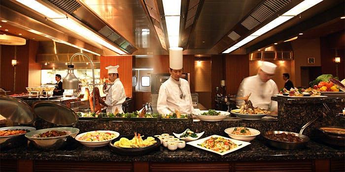 シェフの調理風景と並べられた料理の写真