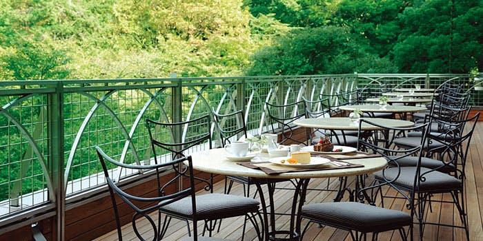 スラッシュカフェのテラス(ケーキや紅茶がのった丸いテーブルと椅子、一面に広がる緑色の木々)