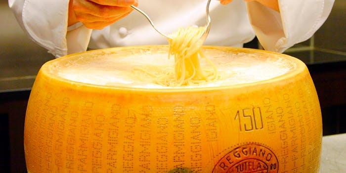 チーズ窯でパスタを和える職人