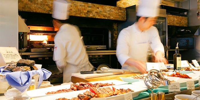 スカイグリルブッフェ武藏のシェフたちがブッフェの料理を素早く作り上げていく写真