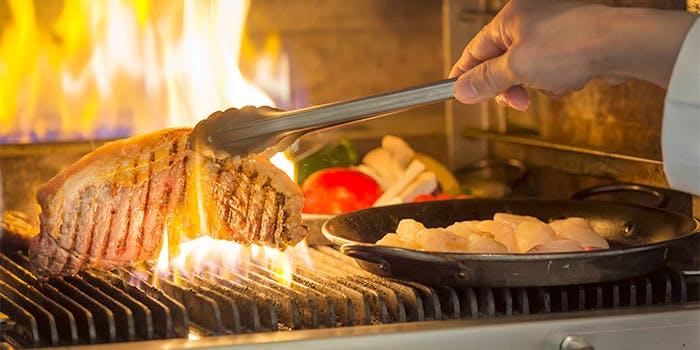 ステーキを豪快に焼きあげる写真
