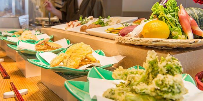 天ぷらや野菜など様々な料理が並んだスカイグリルブッフェ武藏のブッフェの写真