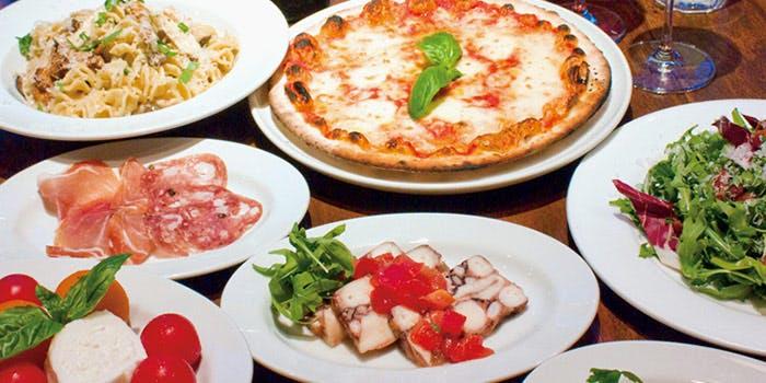 テーブルに並んだピザや生ハムなどのイタリアン