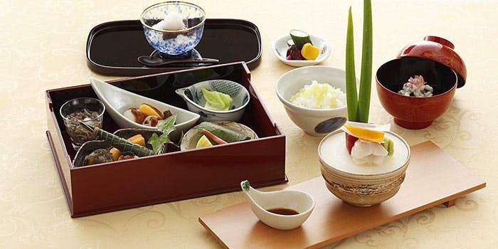 料理がのったいくつかの小皿が詰め込まれた木箱と、ご飯とお椀とデザート