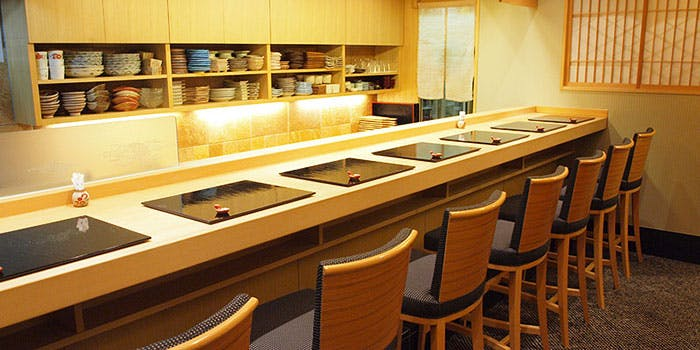純和風の店内に設置された白木のカウンターに、座席が7席分セッティングされている。