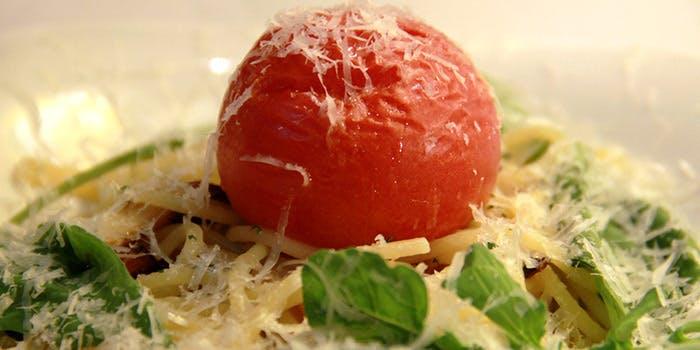 チーズの上にトマトがのった料理写真