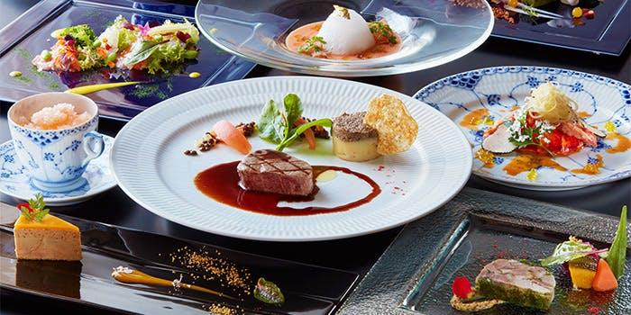 大きな白の皿に盛られた肉料理などのコースメニュー