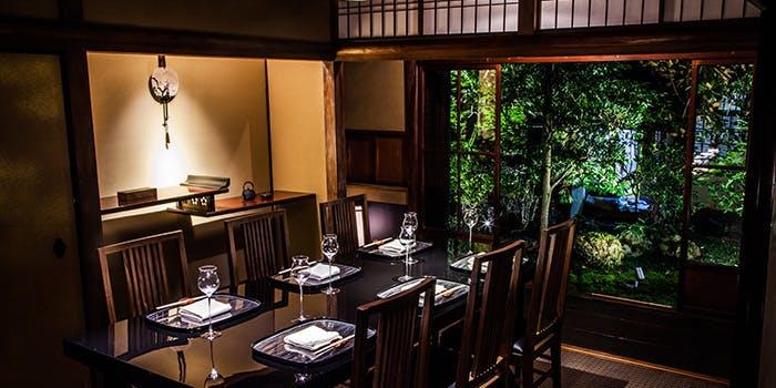 和と洋が融合したクラシカルな和室に、木のテーブルやイスが置かれ、窓の外にはライトアップされた庭園が広がっている。