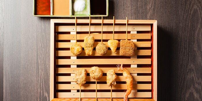 格子状の木のお皿にのった串揚げ10本、塩とタレ4種類
