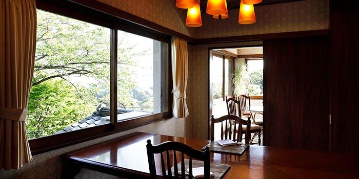 窓から緑の木々が見えるテーブル席